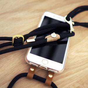 Handyhülle zum Umhängen mit schwarzem Tau und beigen und goldenen Elementen. Die schwarzen Lederdetails zieren deine Handyhülle und machen sie zu etwas ganz besonderem.