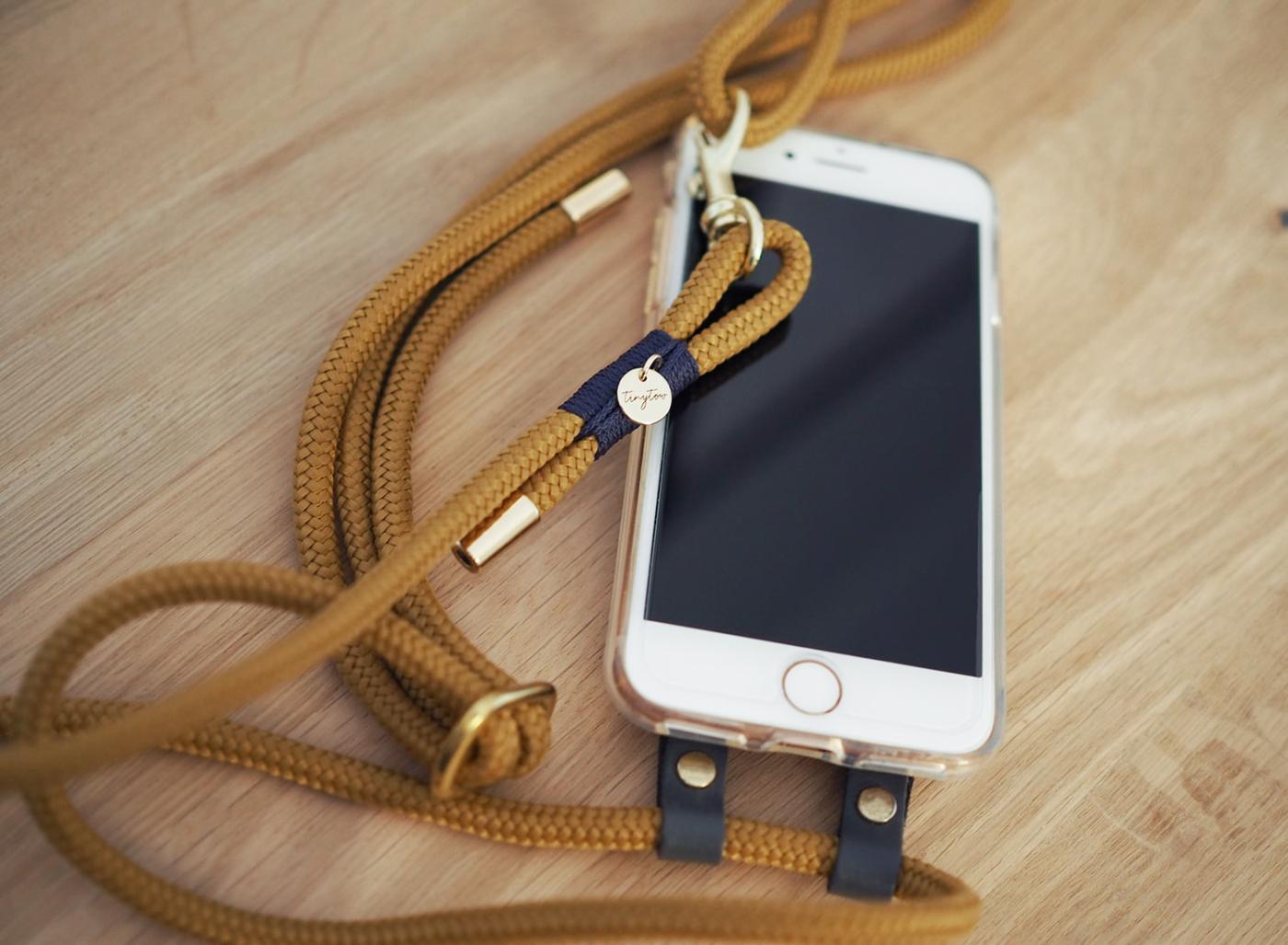 Handyhülle aus Silikon zum Umhängen mit verstellbarem Tau in camel und blau mit goldenen Details.