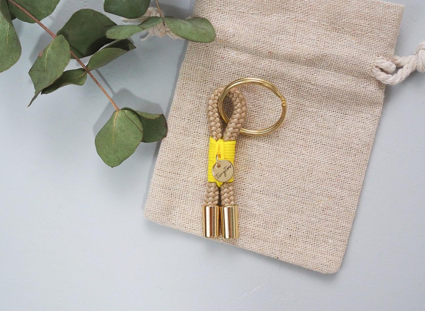 Schlüsselanhänger Towy aus beigefarbenem Tau mit leuchtgelber Takelung, goldenem Schlüsselring und Baumwollsäckchen.