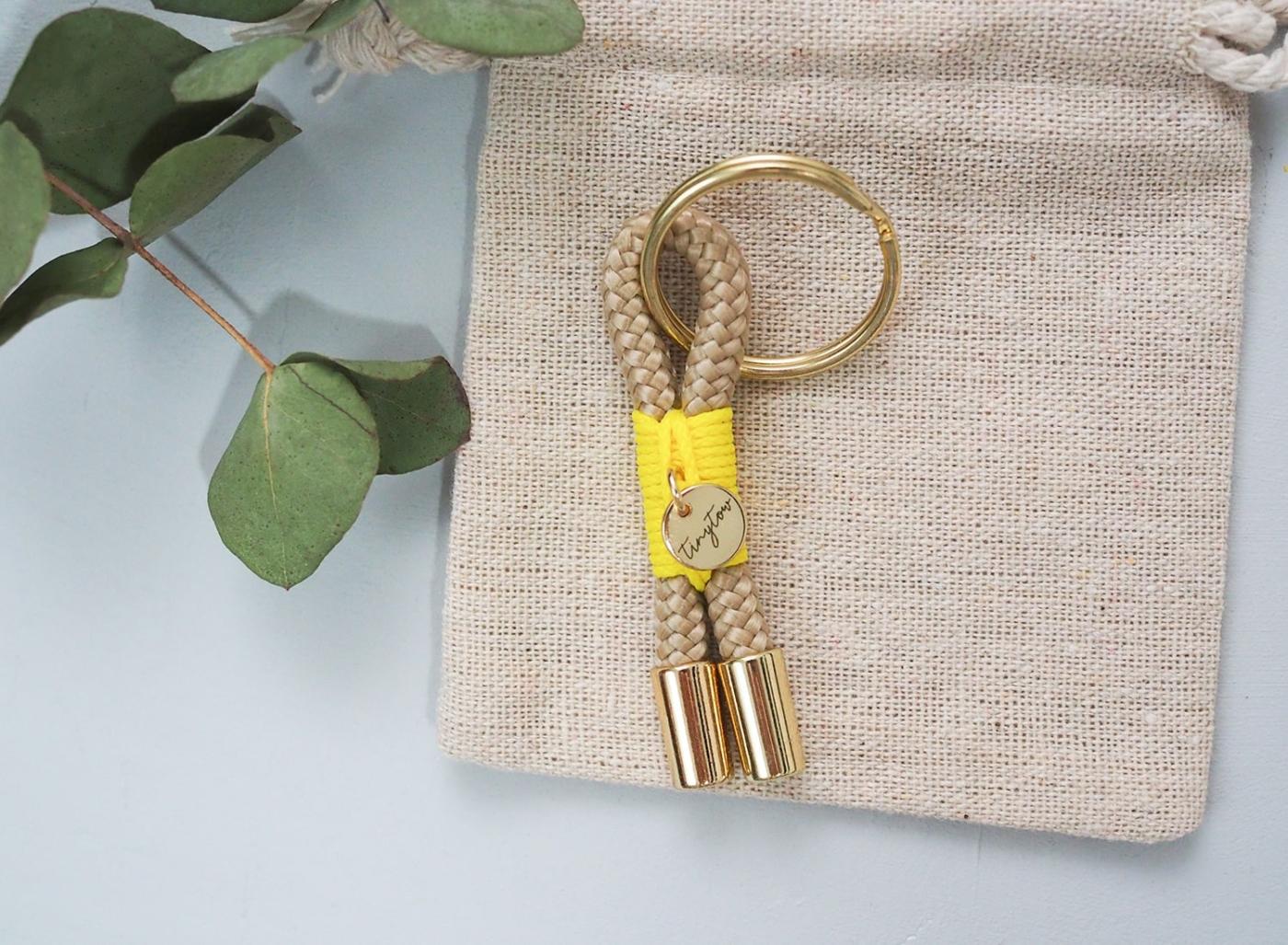 Schlüsselanhänger aus beigefarbenem Tau mit leuchtgelber Takelung, goldenem Schlüsselring.