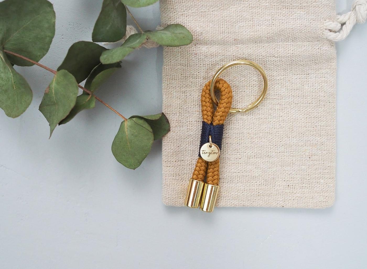 Schlüsselanhänger aus Tau in camel mit blauer Umwickelung (Takelung), goldenen Details und Leinen-Säckchen.