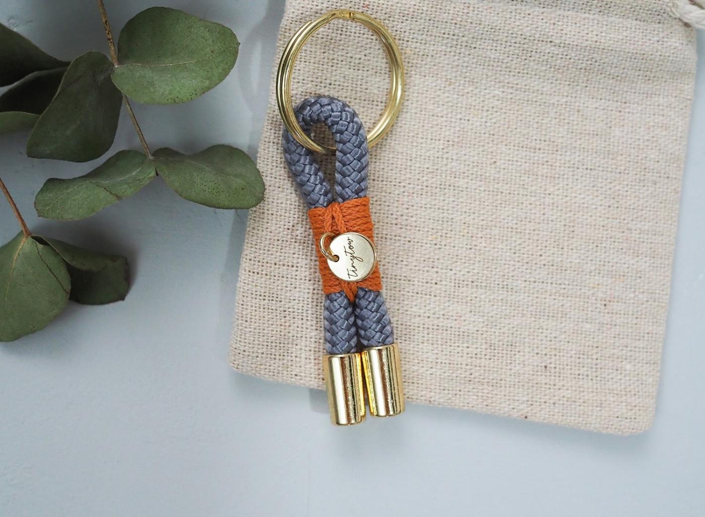 Tau Schlüsselanhänger in grau mit orangefarben Details auf Baumwollsäckchen.