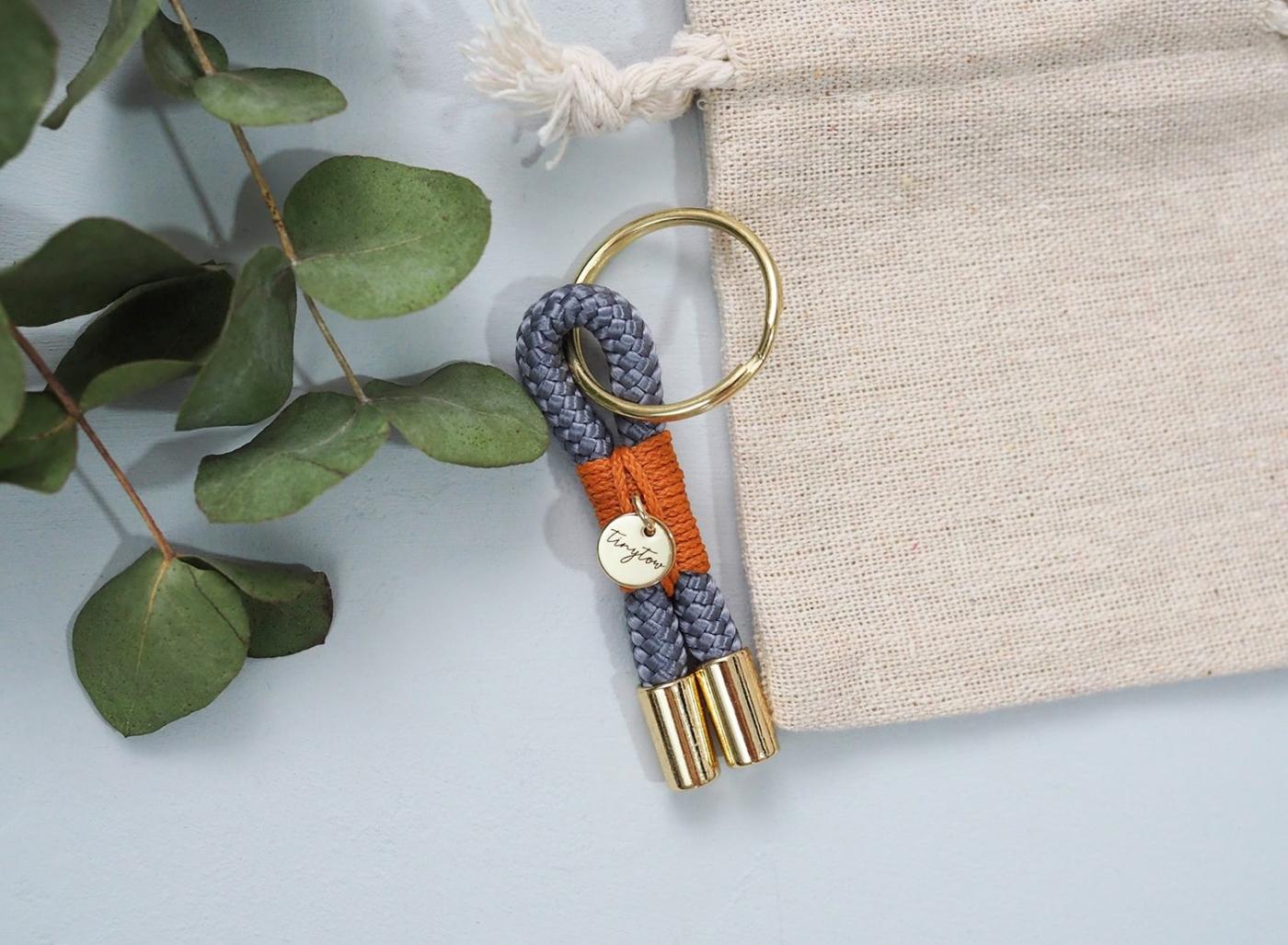 Schlüsselanhänger aus dünnem Tauseil in grau mit goldenen Details und Baumwollsäckchen.