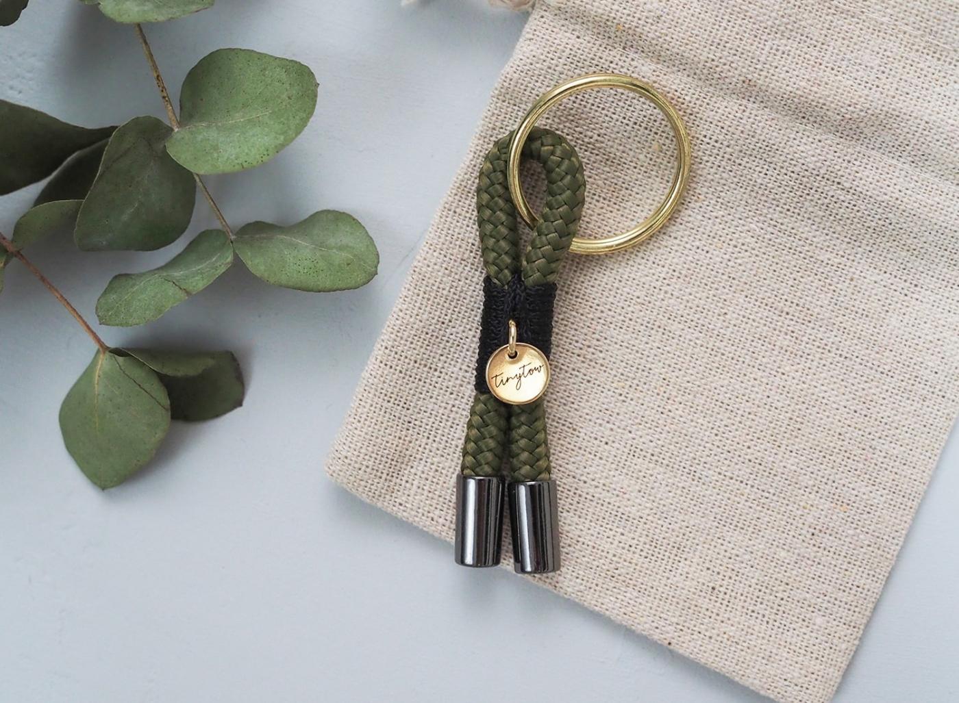 Schlüsselanhänger aus Tau in olivgrün und schwarz mit goldenen Details und beigem Baumwollsäckchen.