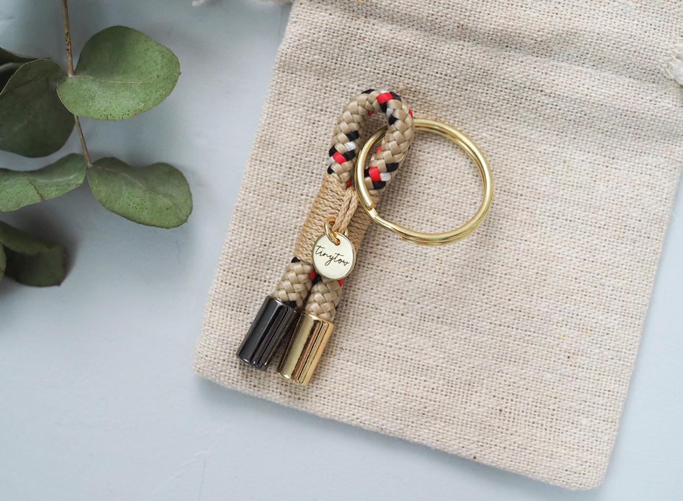 Niedlicher kleiner Schlüsselanhänger aus Tau im Burberry-Look mit beige-rotem Schottenkaro und goldenen Details.