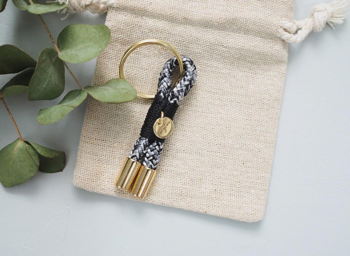 Schlüsselanhänger Towy mit schwarz-weißem Tauseil, schwarzer Takelung und goldenen Details. Liebevoll verpackt in einem Baumwollsäckchen.