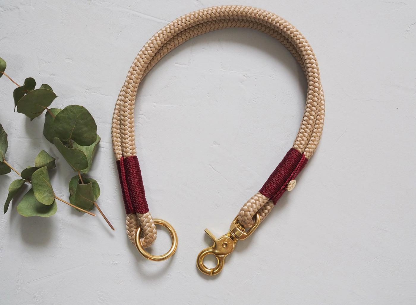 Halsband aus Tauwerk in beige mit weinroter Umwickelun und goldenen Beschlägen aus Messing.
