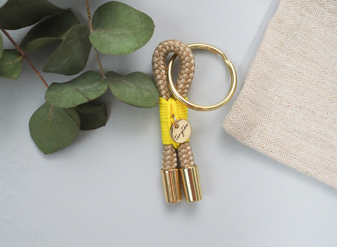 Schlüsselanhänger aus beigefarbenem Tau mit leuchtgelber Takelung, goldenem Schlüsselring und Baumwollsäckchen.