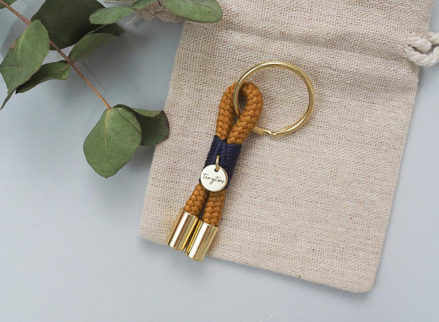 Schlüsselanhänger im Mini-Format aus Tauwerk in camel, blau mit goldfarbenen Details. Liebevoll verpackt und mit größter Sorgfalt hergestellt.