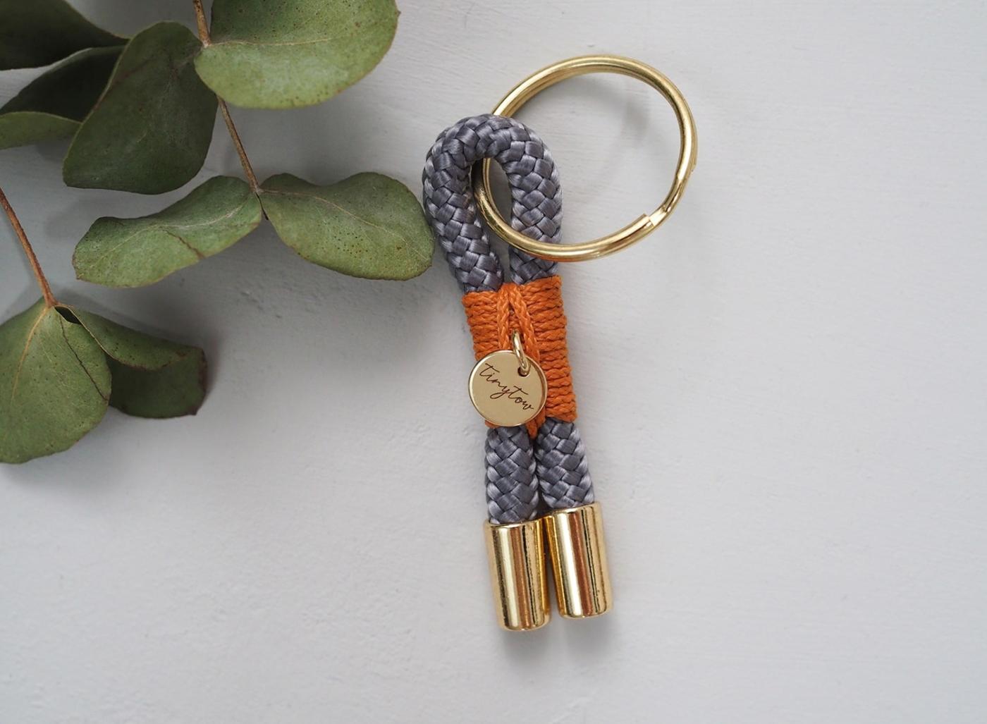 Schlüsselanhänger aus Tauseil in grau mit camelfarbener Umwickelung und goldenen Details.