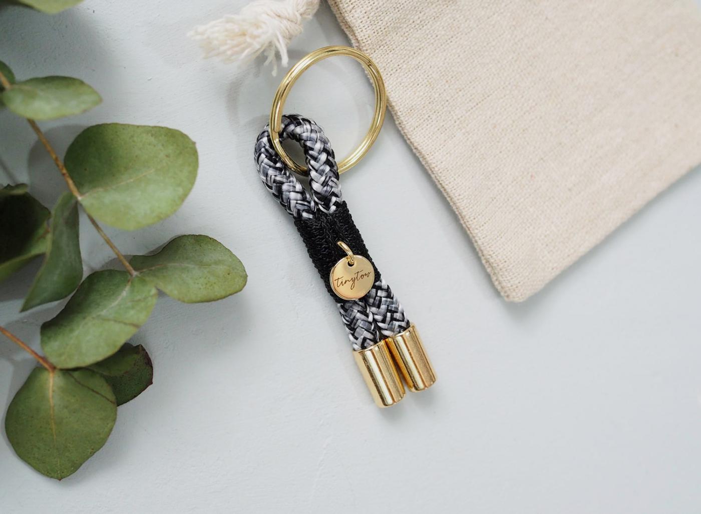 Schlüsselanhänger aus Tau mit schwarz-weißem Tauseil, schwarzer Takelung und goldenen Details.