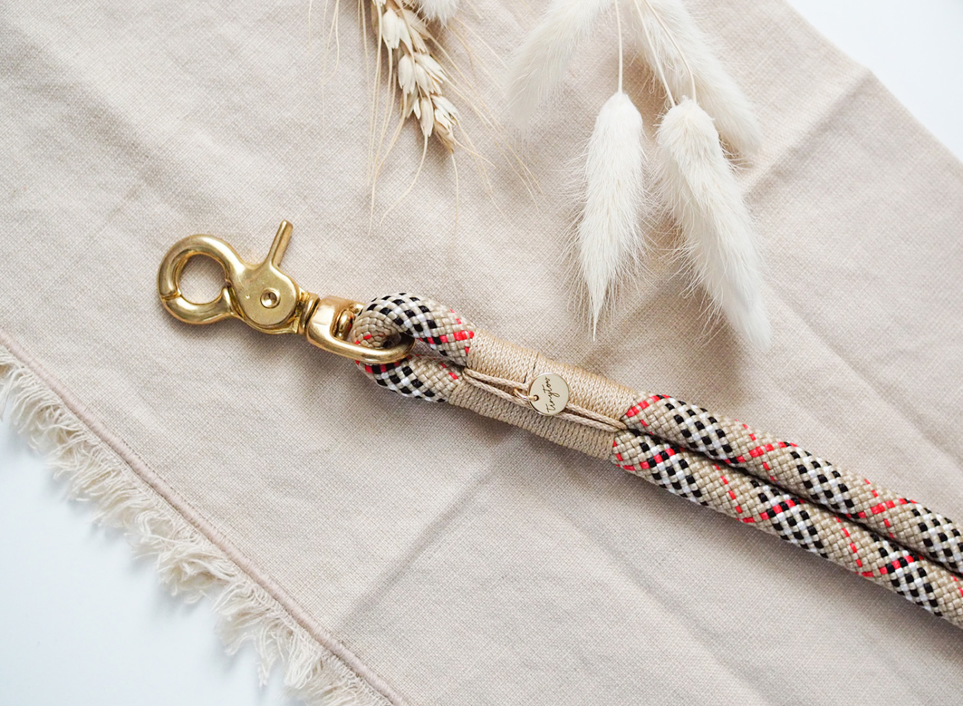 Detailaufnahme unseres Halsbandes aus Tau in kariertem Schottenkaro-Look mit beigen Details und goldenen Karabinern.
