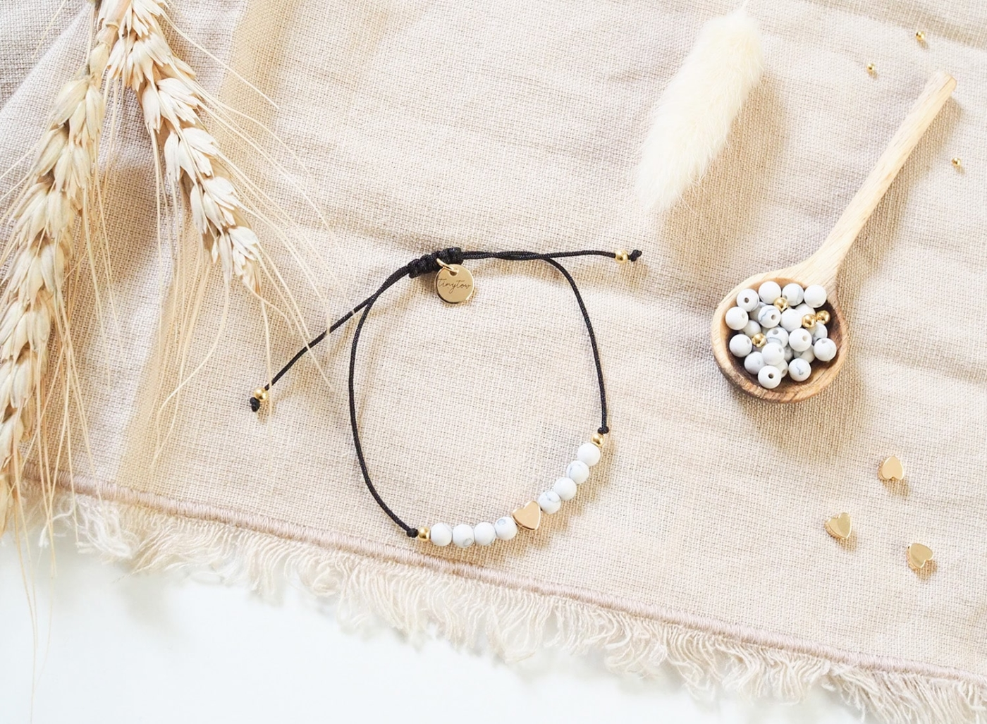 Armband aus weißen Natursteinperlen mit goldenem Herz, schwarzem Makramee-Band und Schiebeverschluss und edlen, goldenen Perlen mit 14k Gold Überzug.