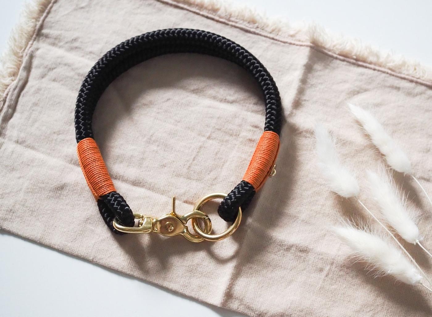 Halsband aus Tauseil in schwarz mit Details in camel und goldenen Karabinern.