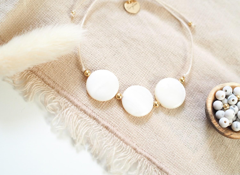 Perlmutt Armband Ariel mit beigefarbenem Makramee-Band, drei schimmernden Perlmuttscheiben in elfenbein und goldfarbenen Perlen.