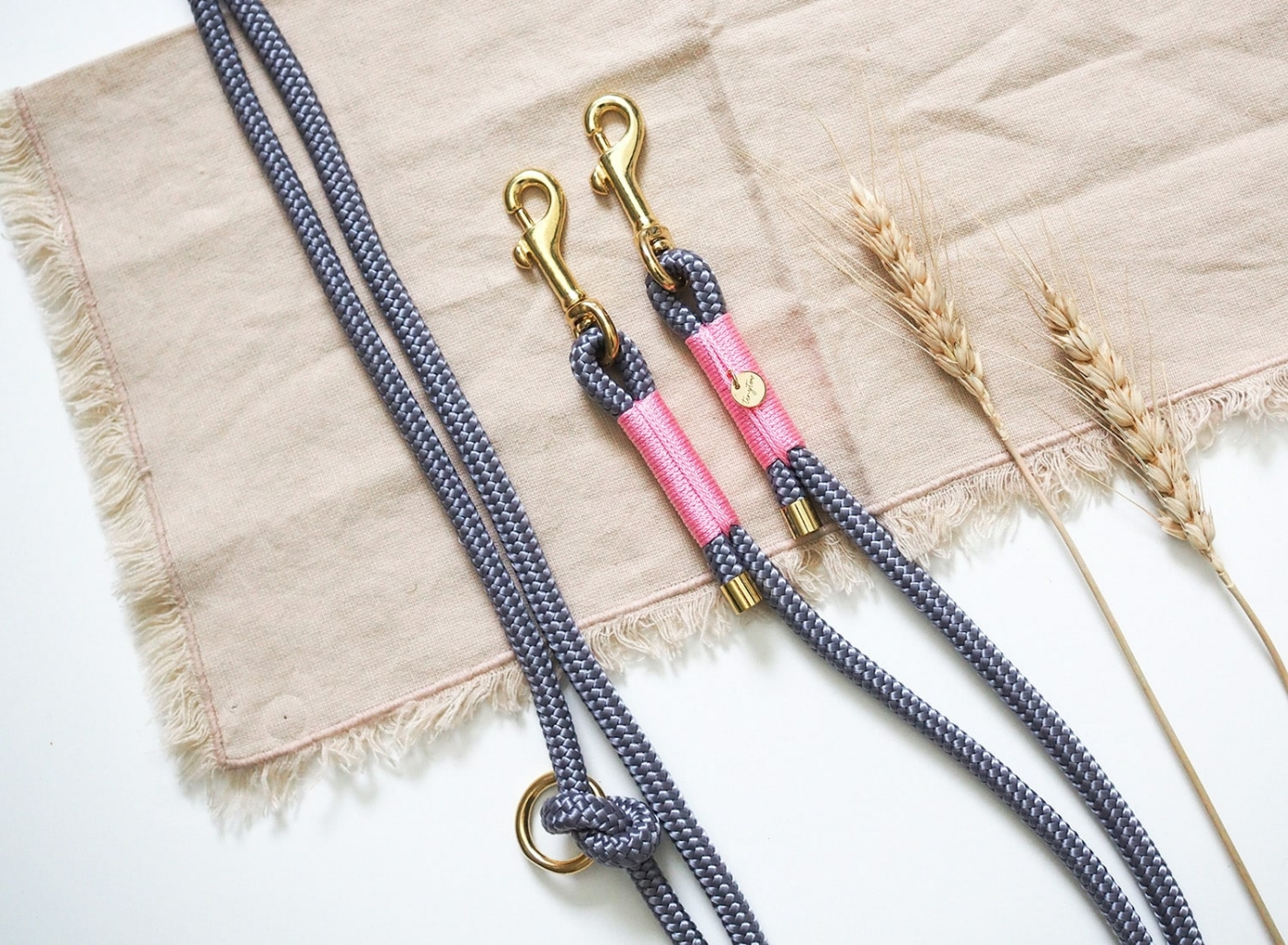Hundeleine aus grauem Tau mit rosa Details und goldenen Karabinern.