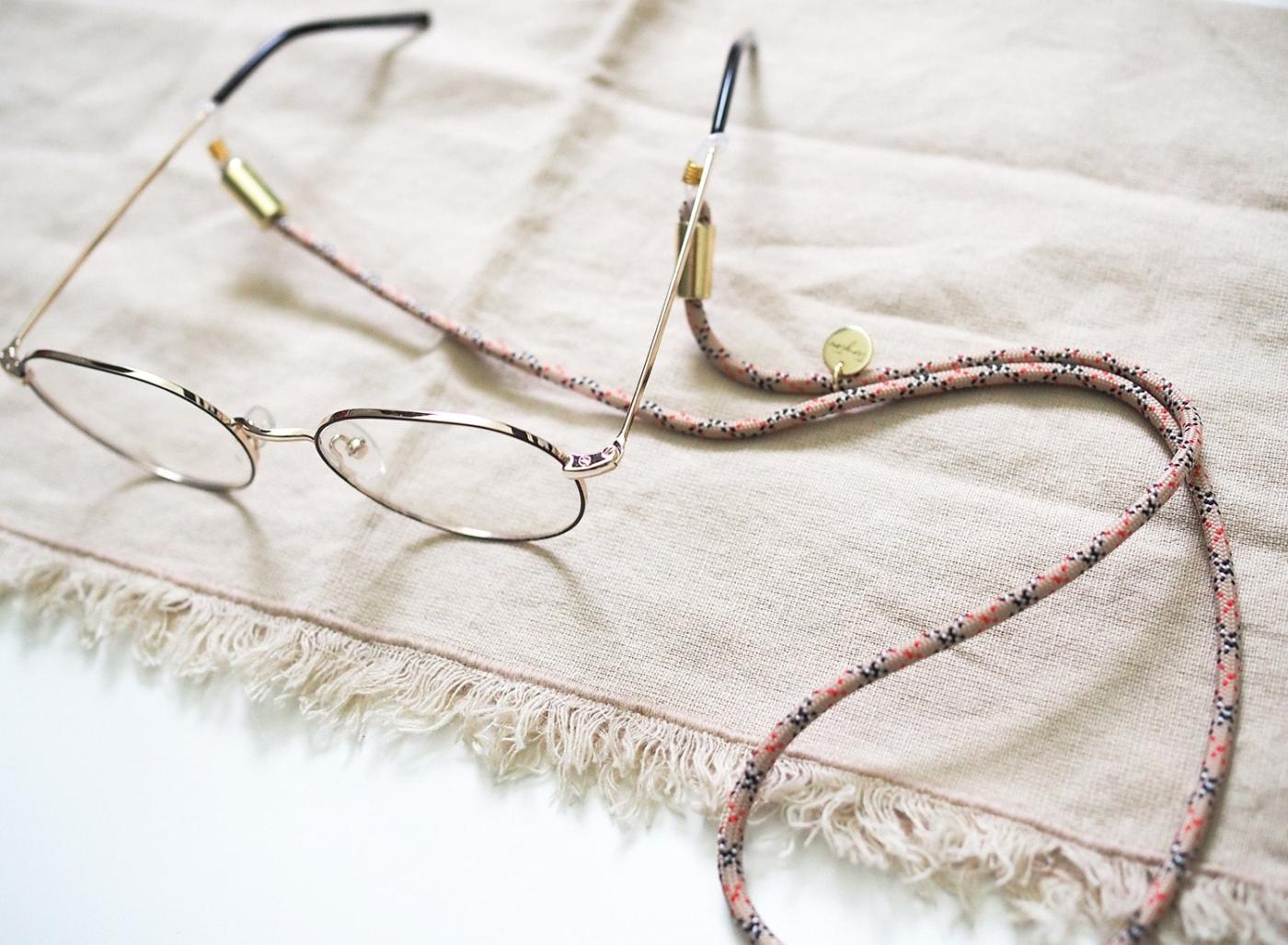Brillenband aus Nylon-Tau in beige kariert an Brille mit goldenen Details.