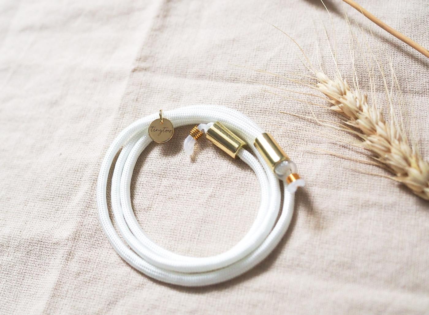 Detailaufnahme Brillenband Betty in weiß mit goldenen Details.