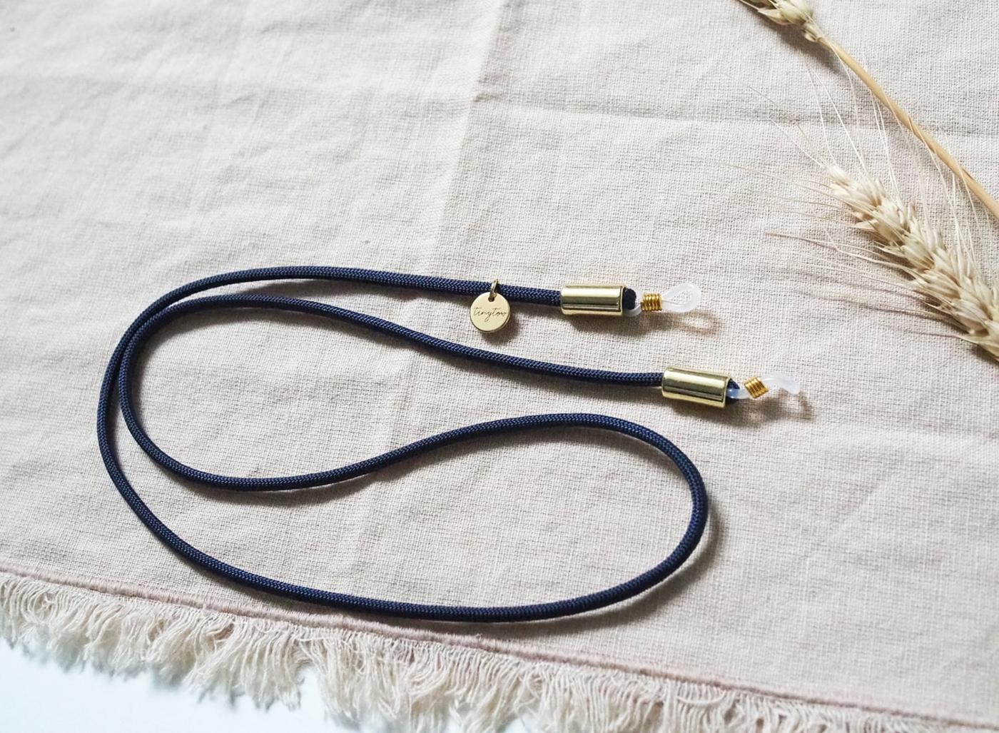 Brillnband in dunkelblau mit goldenen Details aus Nylon/Stoff.