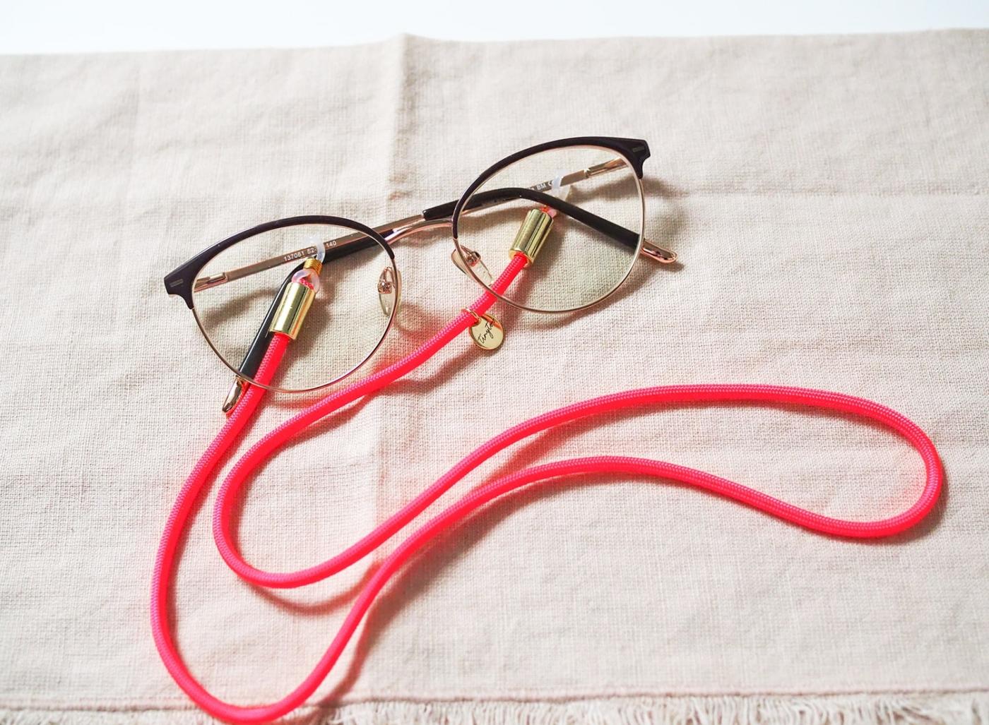 Brillenband in leuchtendem Pink mit goldenen Details.