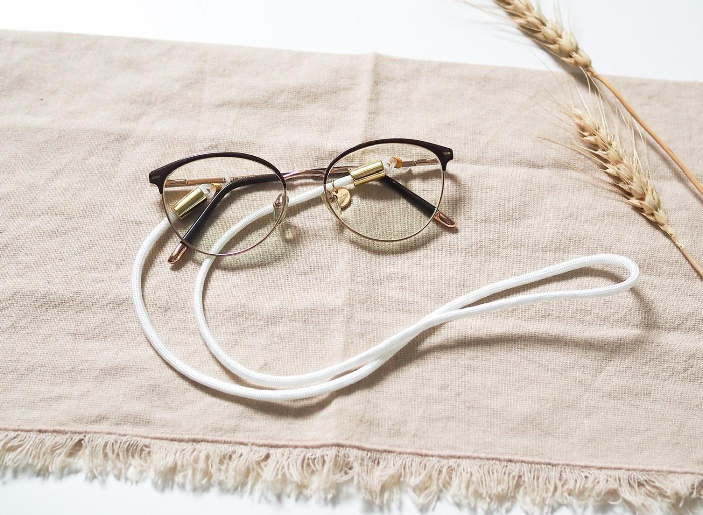 Brillenband aus Nylon/Stoff in weiß mit goldenen Elementen an Brille.