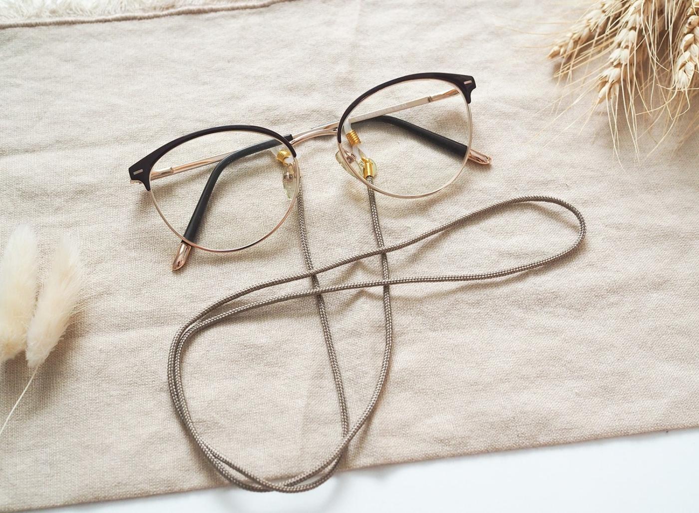 Zartes Brillenband in tan/taupe mit goldenen Details und Silikonschlaufen.