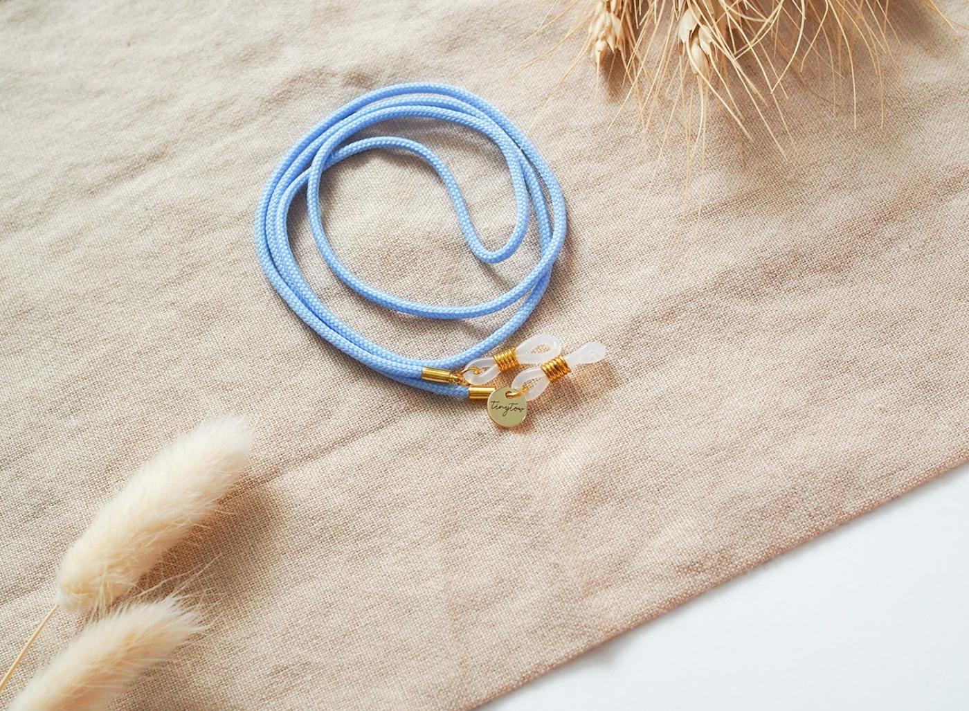 Hellblaues Brillenband mit Silikonschlaufen und goldenen Details.